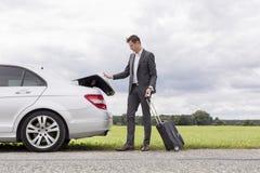 In voller Länge vom jungen Geschäftsmann, der Gepäck von aufgegliedertem Auto an der Landschaft entlädt Lizenzfreies Stockbild