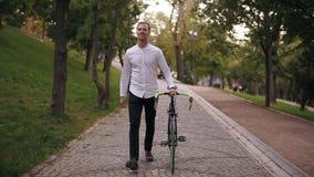 In voller Länge vom lächelnden jungen Mann des Kaukasiers im weißen Hemd gehend mit Fahrrad auf der Straße in der Stadt Rollen se stock video