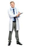 In voller Länge von überzeugtem jungem Doktor auf weißem Hintergrund Lizenzfreies Stockbild