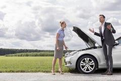 In voller Länge von den Geschäftspaaren, die Argument durch defektes Auto an der Landschaft haben Stockbild
