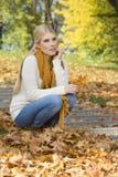 In voller Länge von der durchdachten jungen Frau, die auf Schritten im Park sich duckt lizenzfreies stockbild