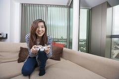 In voller Länge von der glücklichen jungen Frau, die zu Hause Videospiel auf Sofa spielt Lizenzfreies Stockbild