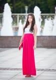 In voller Länge von der jungen kaukasischen Frau mit dem langen roten Rock, der vor einem Brunnen im Freien steht Stockbilder