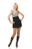 In voller Länge von der jungen lächelnden Frau im Minikleid Stockfoto