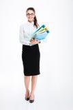 In voller Länge von der netten jungen Geschäftsfrau, die Ordner steht und hält Stockbilder