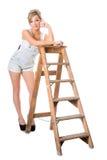 In voller Länge von der recht jungen Blondine, stehend auf altem Stehleiter still Lizenzfreie Stockfotografie