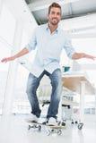 In voller Länge von einem glücklichen jungen Mann, der in Büro Skateboard fährt Lizenzfreies Stockbild
