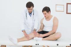 In voller Länge von einem jungen Mann, der sein Knie überprüft erhält Lizenzfreie Stockfotos