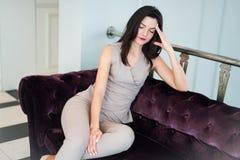 In voller Länge von einer eleganten jungen Frau, die zu Hause mit Kopf in den Händen auf Sofa sitzt lizenzfreies stockbild