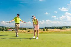 In voller Länge von einer Frau, die professionellen Golf mit ihrem männlichen Matchpartner spielt Lizenzfreie Stockfotos