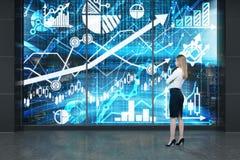 In voller Länge von junger Dame, die vor dem digitalen Schirm mit Diagrammen, Diagrammen und Pfeilen steht Ein Konzept des Kapita Lizenzfreie Stockbilder