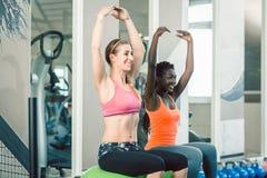 In voller Länge von zwei geeigneten Frauen, die auf Eignungsbällen beim Trainieren sitzen lizenzfreie stockfotos