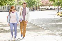 In voller Länge vom jungen Mann und weiblichen von den Studenten, die auf Fußweg gehen Lizenzfreie Stockfotos