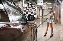 In voller Länge vom Modell mit Rennflagge an der Waschanlage Stockbild