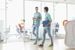 In voller Länge von den Geschäftsmännern, die am kreativen Arbeitsplatz gehen Stockfotos