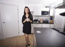 In voller Länge von der durchdachten jungen haltenen Kaffeetasse in der Küche Lizenzfreie Stockfotos