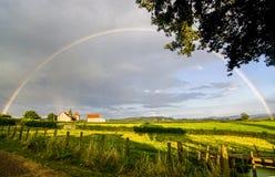 Voller Regenbogen mit untergehender Sonne Lizenzfreie Stockfotos