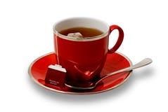 Voller roter Teacup und Saucer mit dem Teebeutel ein getrennt Lizenzfreie Stockfotos