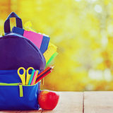 Voller Schulrucksack mit rotem Apfel auf hölzernem und Herbstnaturhintergrund Stockbilder