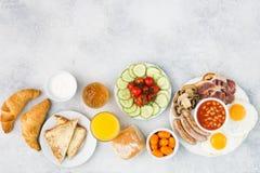 Volles englisches Frühstück, Eier, Speck, Würste, Brote und Früchte Stockbild