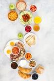 Volles englisches Frühstück, Eier, Speck, Würste, Brote und Früchte Stockfotografie