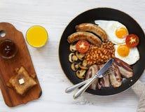 Volles englisches Frühstück in einer Wanne mit Spiegeleiern, Speck, Bohnen, Würsten und Toast auf einem weißen hölzernen Hintergr Lizenzfreies Stockfoto