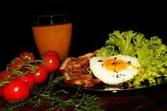 Volles englisches Frühstück mit durcheinandergemischten Eiern, Speck, Bohnen, Tomaten und Orangensaft Schwarzer Hintergrund Stockfoto