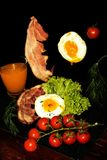 Volles englisches Frühstück mit durcheinandergemischten Eiern, Speck, Bohnen, Tomaten und Orangensaft Schwarzer Hintergrund Lizenzfreie Stockfotografie