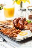 Volles englisches Frühstück mit Speck, Wurst, Ei, backte Bohnen und Stockbilder
