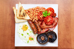 Volles englisches Frühstück mit Speck, Wurst, Ei, Bohnen und Pilzen Stockfotografie