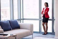 Volles Körperbild der überzeugten schwarzen Geschäftsfrau im Geschäftsaufenthaltsraum Lizenzfreies Stockbild