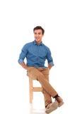 Volles Körperbild des entspannten Sitzmannes, der zur Seite schaut Stockbild
