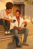 Volles Körperglückliches paar, das draußen auf Bank mit Telefon und Lebensmittel sitzt Stockbild