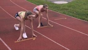 Volles leight von zwei herrlichen weiblichen Läufern in Anfangsposition auf Stadion Jugendlicher gesund, Sportleutekonzept stock footage