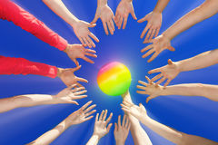 Volley ball. Several hands reaching out together in a circle for volley ball against blue sky Royalty Free Stock Photos
