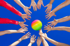 Volley ball. Several hands reaching out together in a circle for volley ball against blue sky Stock Photo