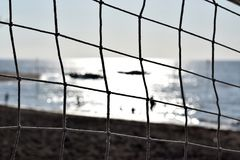 Volley ball net obscure the view of people bathing on the sea. selective focus,. Silhouettes Royalty Free Stock Image