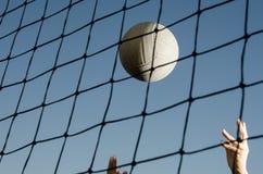 Volleyball achter netto met handen Stock Fotografie