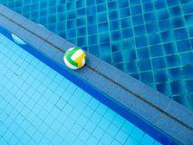 Volleyball ball floats in the blue pool stock photos