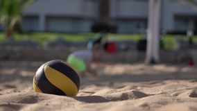 Volleyball ball on foreground, little baby on background walk and fall. stock video footage
