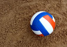 Volleyball ball lies on the sand and waits for its player stock image