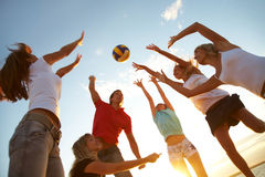 Volleyball on the beach. Group of young people playing volleyball on the beach royalty free stock image