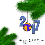 Volleyball and 2017 on a Christmas tree branch. Happy New Year and numbers 2017 and volleyball ball as a Christmas decorations hanging on a Christmas tree branch Royalty Free Stock Image