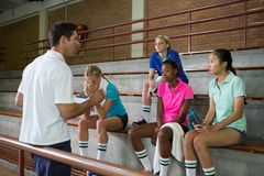 Volleyball coach instructing to female players. In court Royalty Free Stock Images