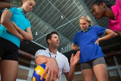 Volleyball coach talking to female players. In court royalty free stock image