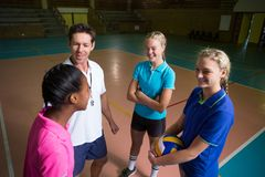Volleyball coach talking to female players. In court Stock Photo