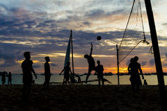 Volleyball de plage, coucher du soleil, silhouettes des joueurs sur la mer Images stock