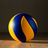 Volleyball on the floor. Ball lying in the sun on a wooden flloor Stock Images