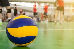 Volleyball on the floor in the gym, team of athletes is a bunch. Yellow-blue volleyball on the floor in the gym, team of athletes is a bunch royalty free stock photo