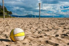 Volleyball Waits for Players on Sand Court at Beach Royalty Free Stock Photos